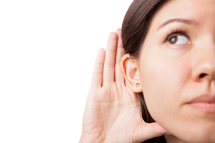 Woman holds her hand near ear and listens carefully